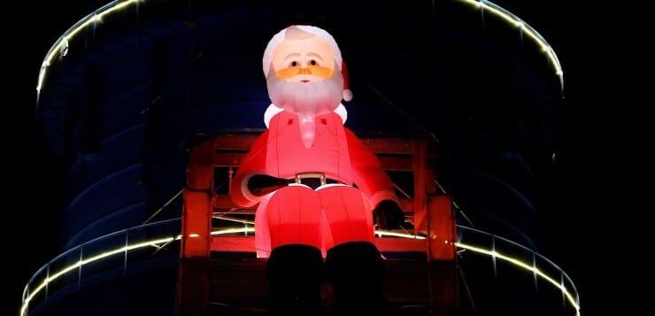 Riesiger beleuchteter aufblasbarer Weihnachtsmann als Kantenhocker am Gaskessel in Bernau bei Berlin